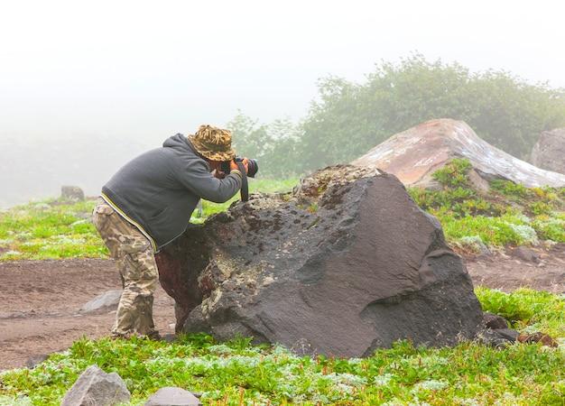 Фотограф в тумане фотографирует природу.