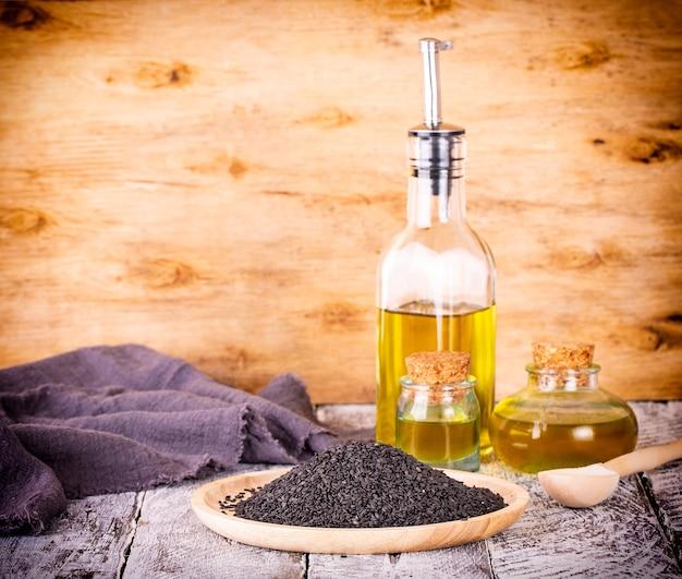 黒胡麻と古い木製の背景に油