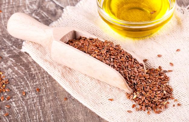 茶色の亜麻の種子と木の表面に亜麻仁油
