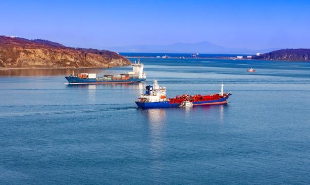 青い海で大型コンテナー船と冷凍船
