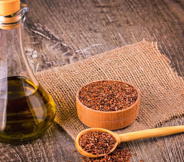茶色の亜麻の種子と木製の表面に亜麻仁油
