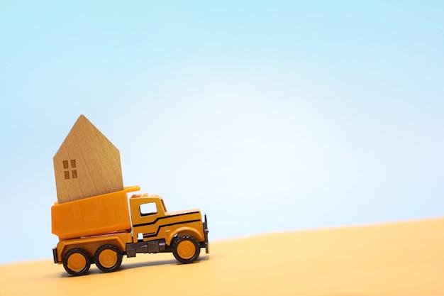 おもちゃのトラックは日光の下で砂漠の家図を運ぶ