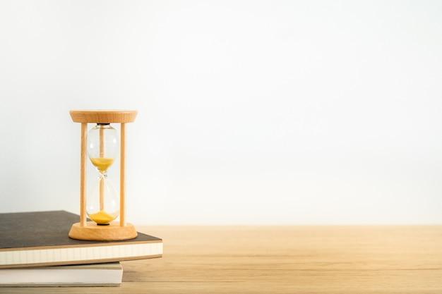 木製のテーブルの上の黒い本の砂時計。時間管理の概念