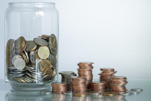 Стеклянные стеки копилки и монетки на таблице с космосом экземпляра для концепции дела и сбережений.