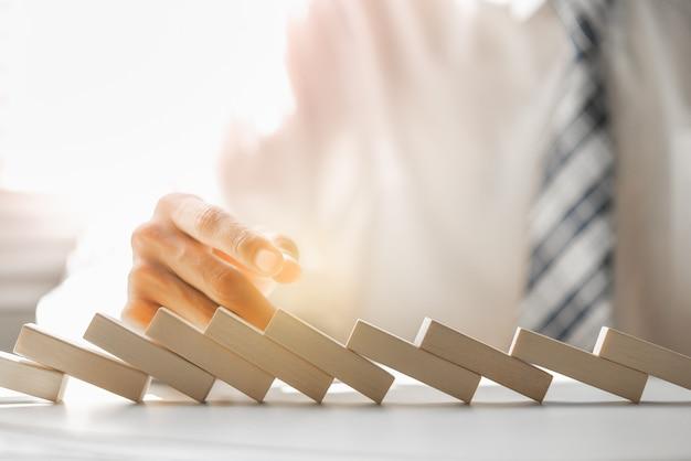ビジネスマンは木製のブロックのドミノ効果を停止しようとして失敗しました。