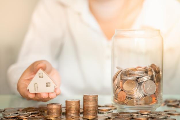 テーブルの上のコインスタックとガラスの瓶と家の図を保持しているクローズアップ女性。ビジネスと貯蓄のお金の概念。