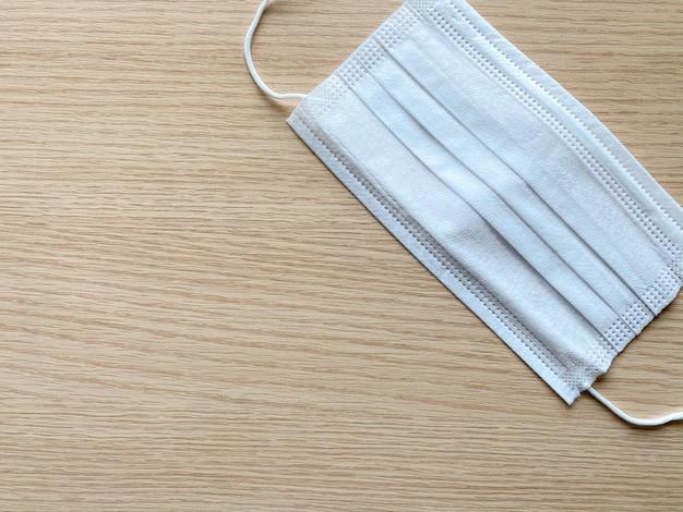 Маска для лица или хирургическая маска лежит на деревянный стол с копией пространства.