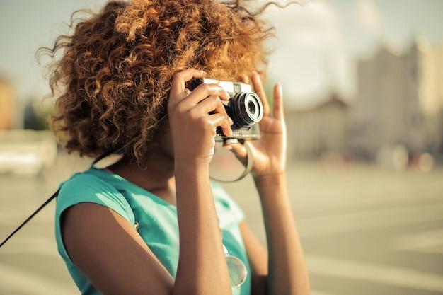 アフロの女性がカメラで写真を撮る