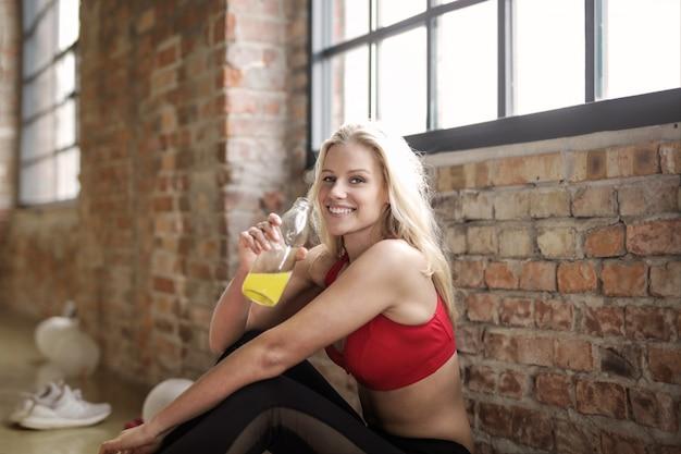 金髪の女性がジムでジュースを飲む