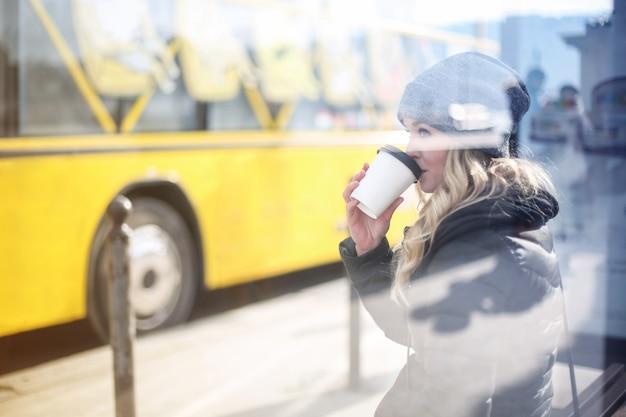 金髪女性がバス停でコーヒーを飲む