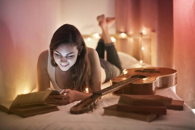 Девочка-подросток пишет на своей кровати