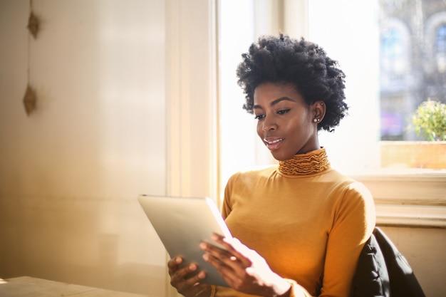 アフロ女性がタブレットで読書