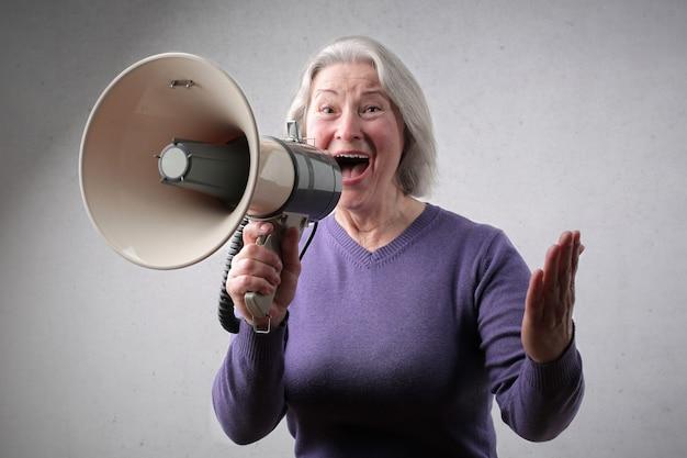 メガホンに話している年配の女性