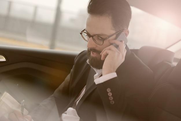 車の中で携帯電話で話している実業家