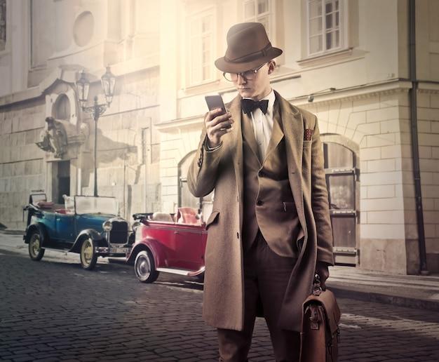スマートフォンとビンテージスタイルの実業家