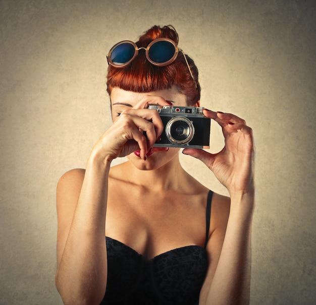 写真を撮る赤髪の女