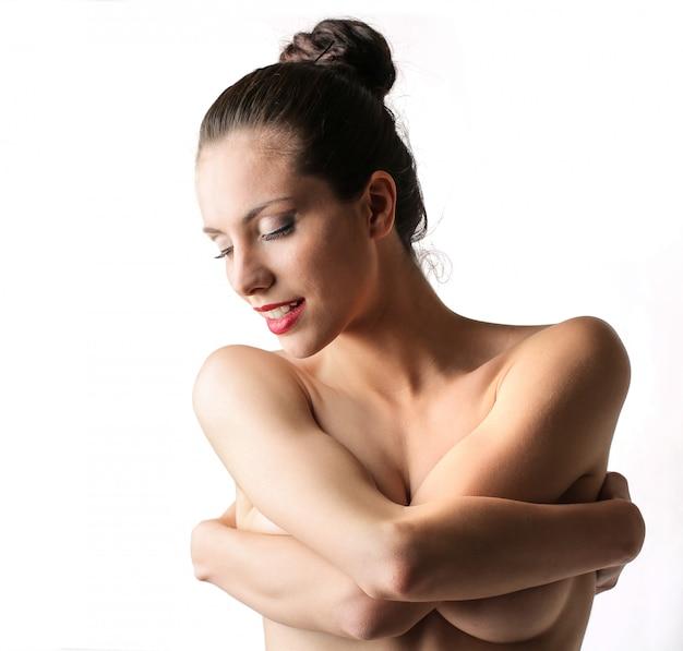 自分を抱き締める裸の女性