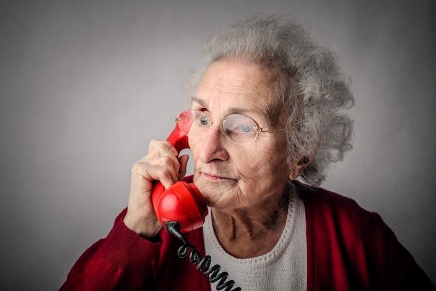 Старушка разговаривает по телефону