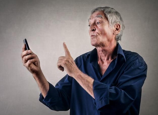 スマートフォンを持つ老人