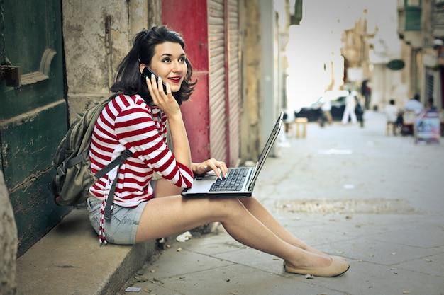 街の休憩にラップトップを持つ少女