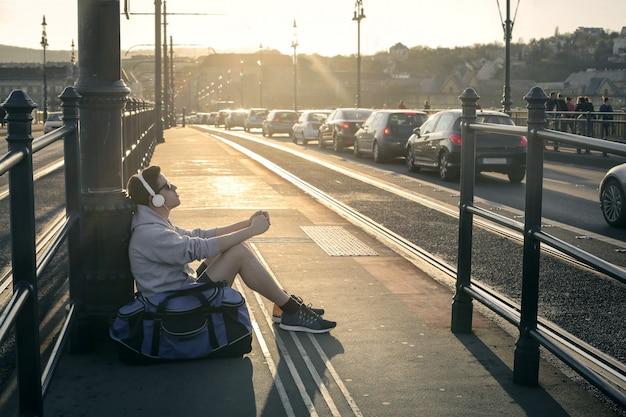 市内のトラム停留所で学生の少年