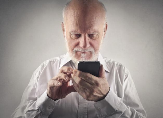 Пожилой мужчина с помощью смартфона