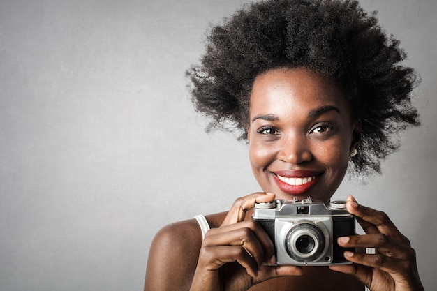 カメラを持つ美しいアフロ女性