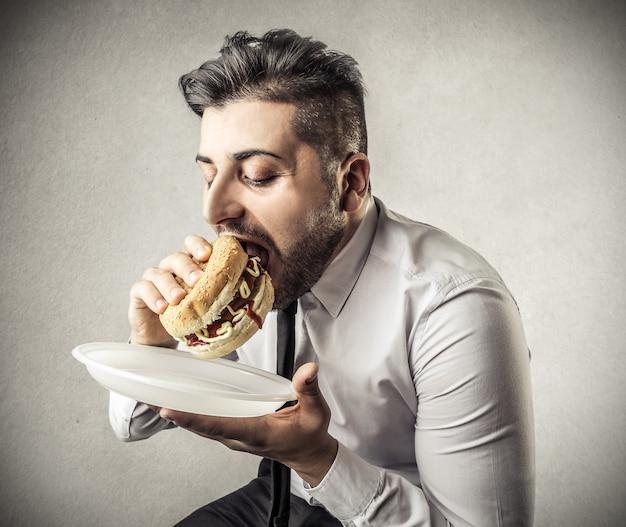 不健康なハンバーガーを食べる