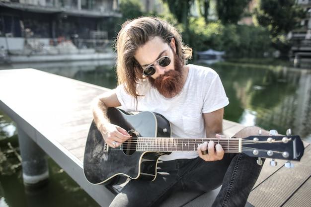スタイリッシュなひげを生やした男がギターを弾いて