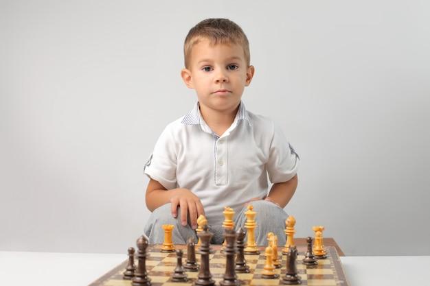 Маленький мальчик играет в шахматы