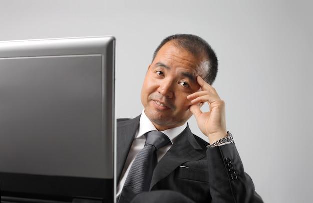 彼のコンピューターを持つアジア系のビジネスマン