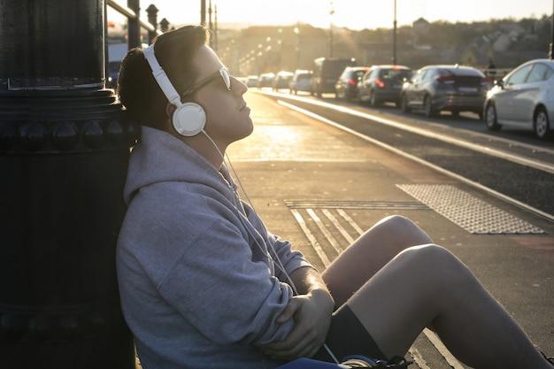 若い男が路上で音楽を聴く