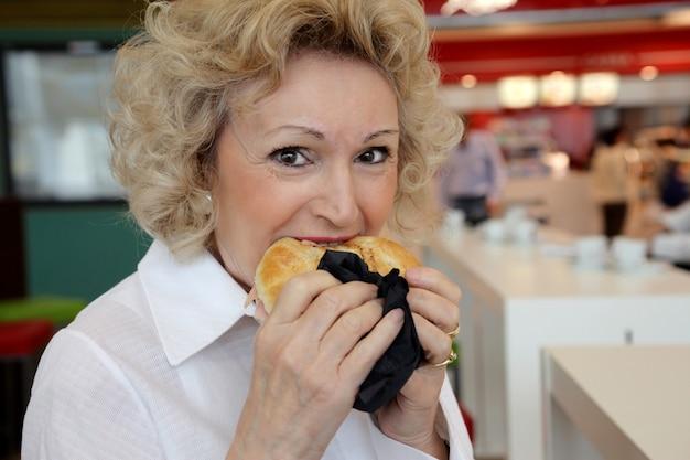 ベーグルを食べる年配の女性