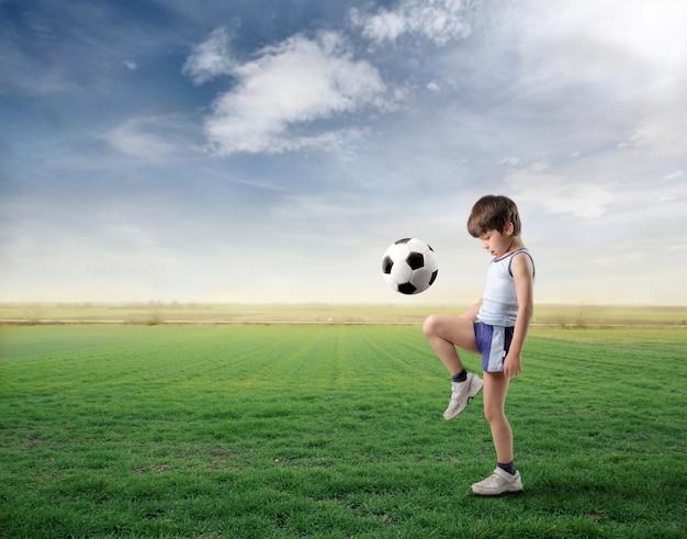 Маленький мальчик играет с футбольным мячом