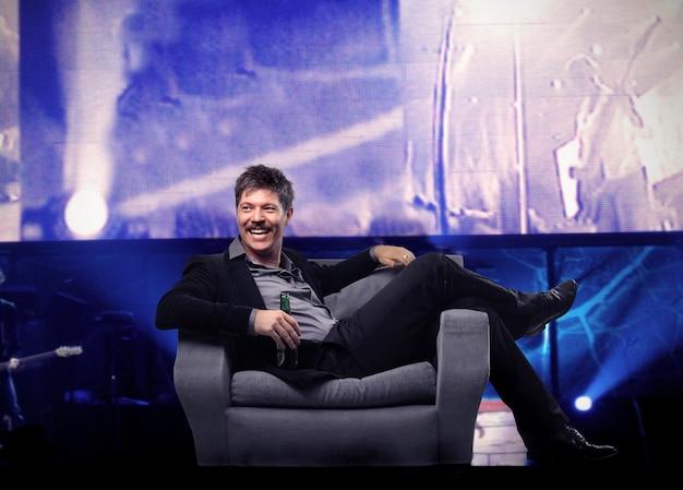 コンサートの肘掛け椅子に座って幸せな笑い男