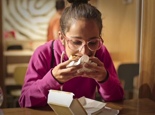 サンドイッチを食べる十代の少女