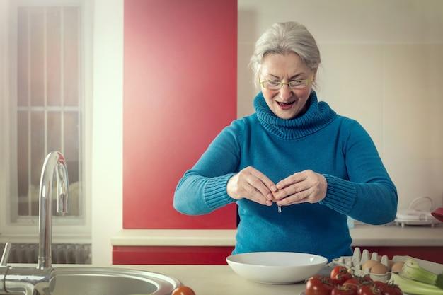 年配の女性が台所で料理をする