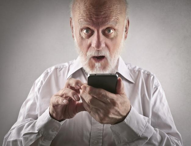 Старший мужчина с помощью смартфона