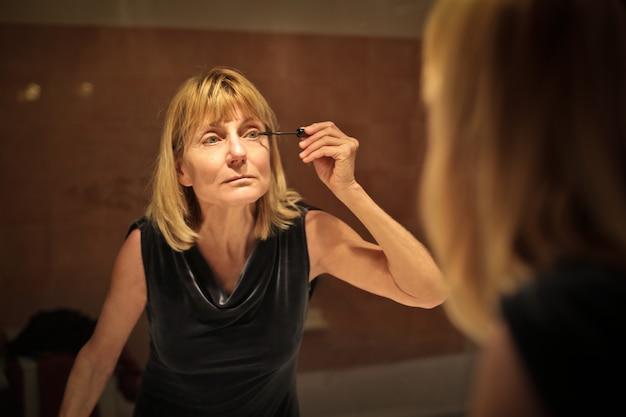年配の女性がマスカラーを適用する