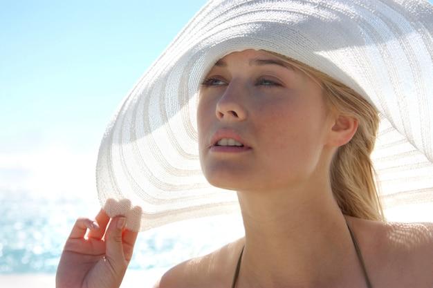 海で帽子を持つ美しい少女の肖像画