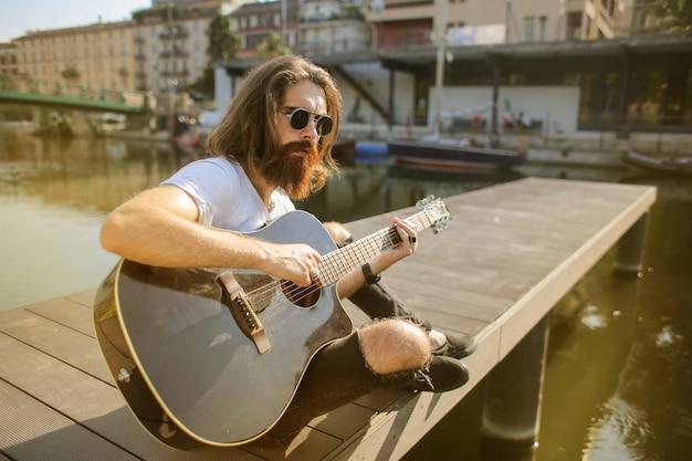 流行に敏感な男がギターを弾いて