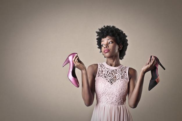 スタイリッシュなアフロ女性は靴のペアをウィット