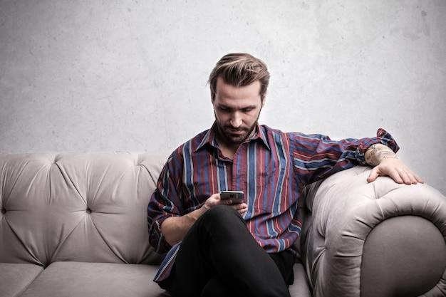 ハンサムな男が彼のスマートフォンをチェック