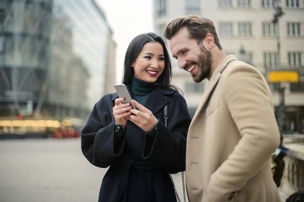 幸せなカップルが彼らのスマートフォンをチェック