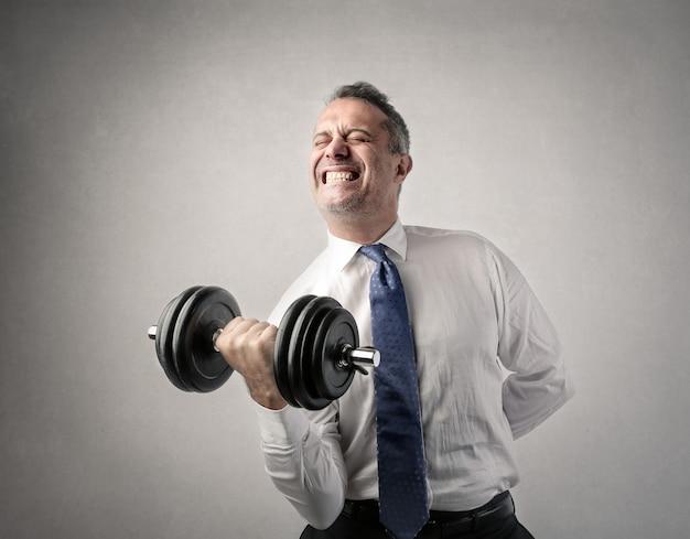 重量を持ち上げようとしている実業家