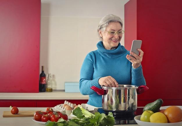 年配の女性が料理をし、彼女のスマートフォンをチェック