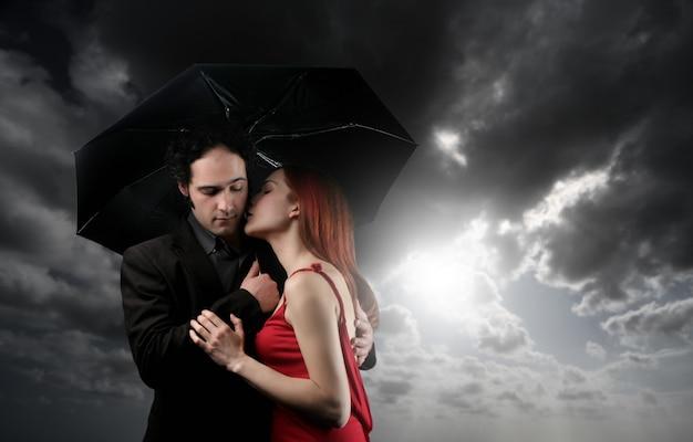 若いカップルが傘の下でキス