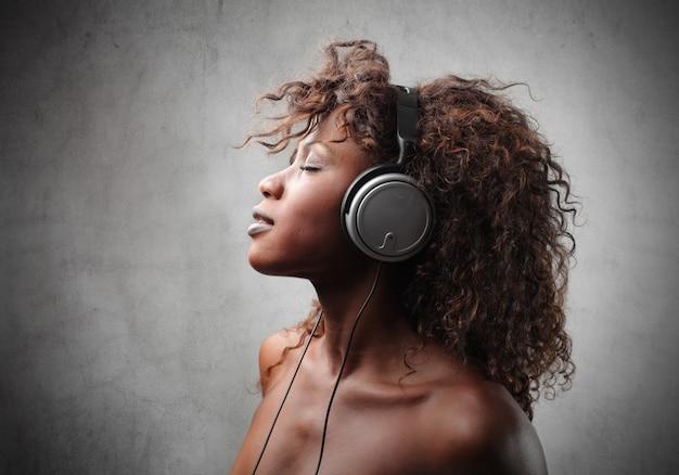 Красивая афро женщина слушает музыку