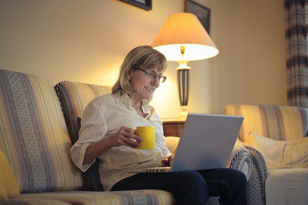 年配の女性がラップトップに取り組んで