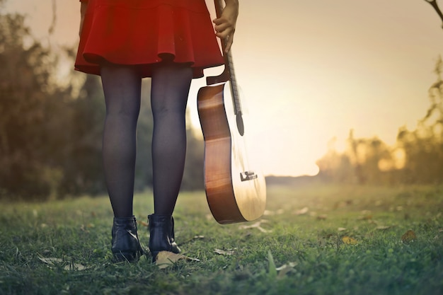 夕日にギターを持つ少女